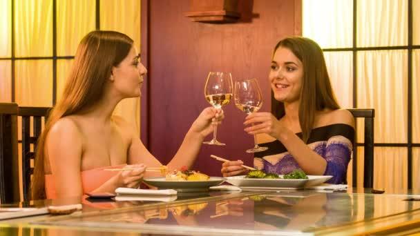 Dvě s úsměvem mladých žen sedí v stylové japonské restauraci