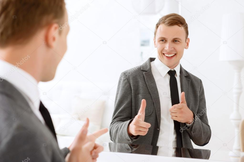 man looking in mirror and pointing on himself stock photo