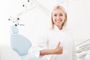 Young smiling female doctor thumbing-up