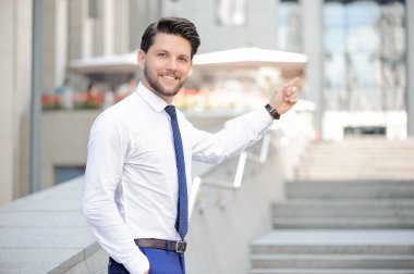 Nice young  businessman pointing up