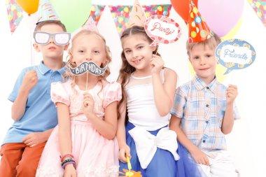 Children holding little birthday tags
