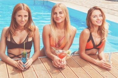 Three girlfriends with cocktails at pool
