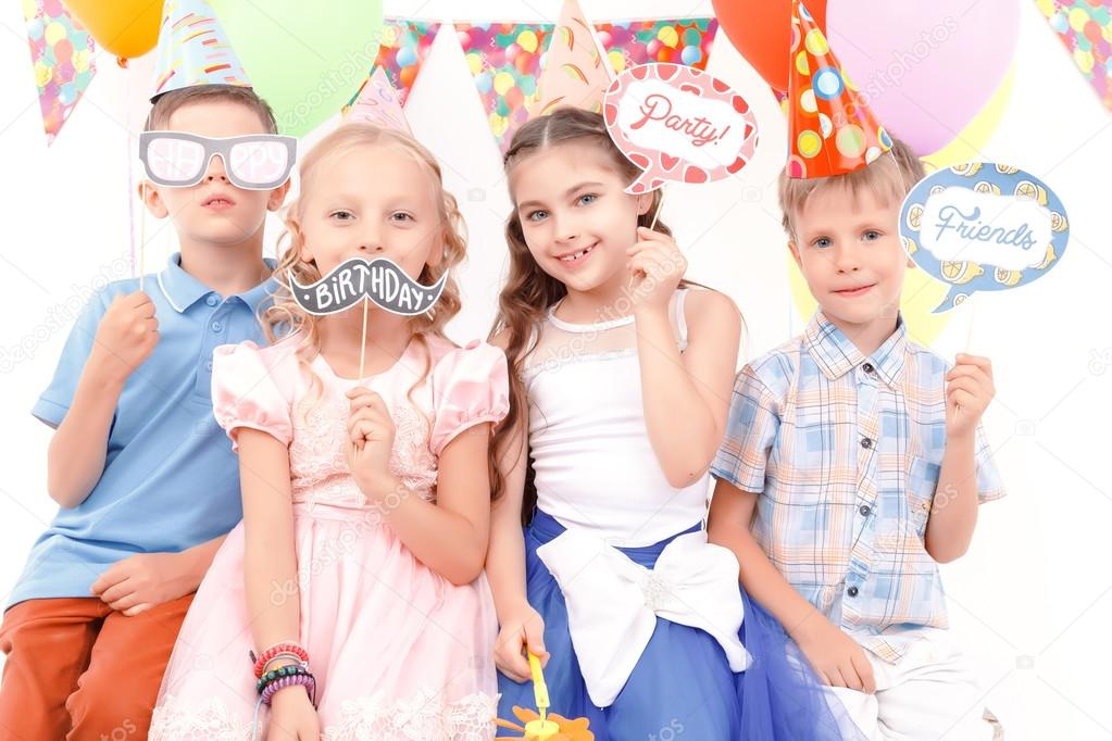 Children holding little birthday tags