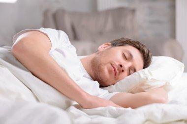 Handsome guy sleeps in his bed.