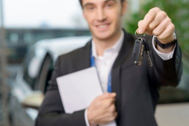 Young salesman is upholding the car keys.