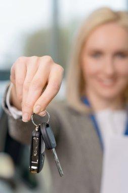 Saleswomans hand grasping the car keys.