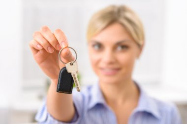 Young woman upholding room key.