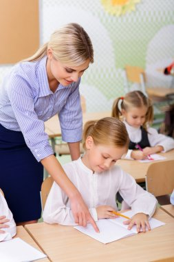 Teacher helps little girl with the task.