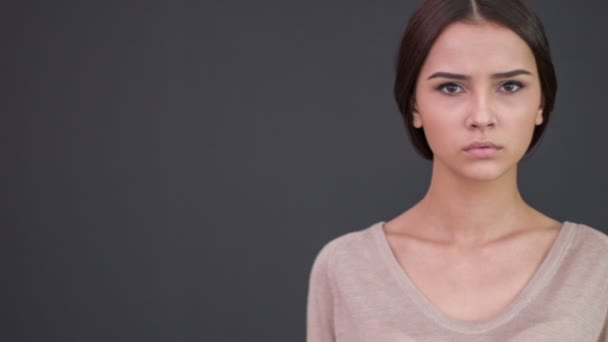 Mladá žena unaveně vypadá naštvaný.
