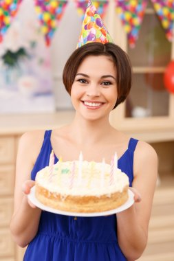 Young smiling girl is holding her birthday cake.