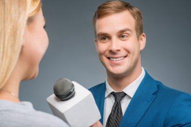 Smiling newsman taking an interview.