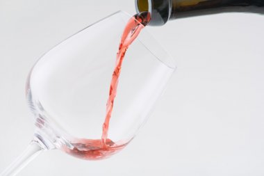 Wine is being poured into the glass.