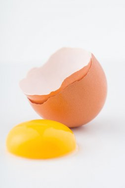 Eggshell with yolk outside of it on the surface.
