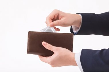 Male hand putting condom into the wallet.