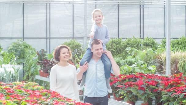 Mladá rodina výběru květiny ve skleníku