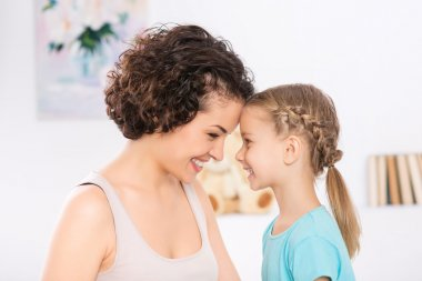 Mother and daughter are grinning to each other.