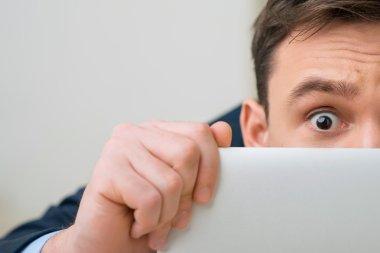 Pleasant office worker hiding behind laptop