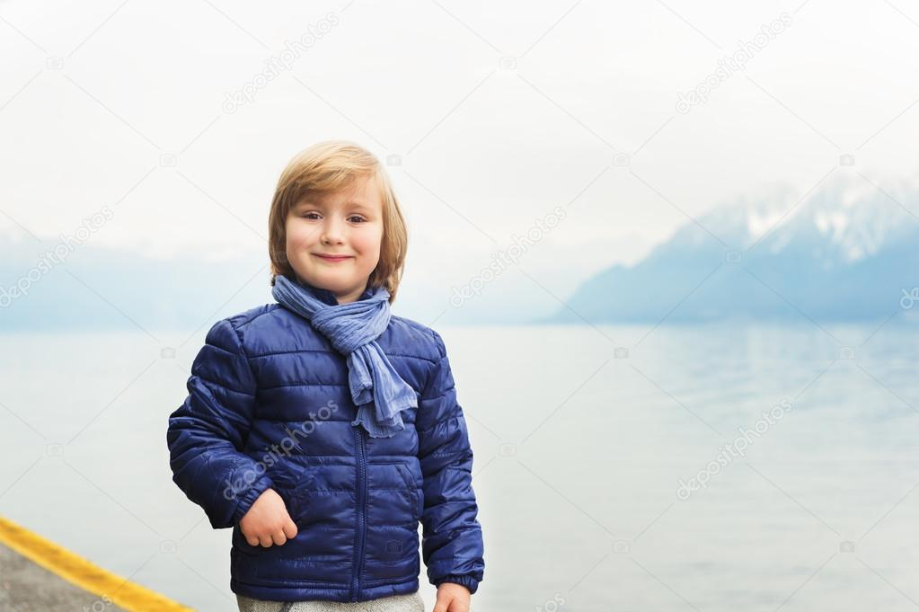 Outdoor portrait of adorable little blond boy of 4-5 years old, wearing blue jacket and scarf, standing by the lake on a cloudy day