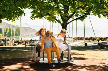 Three kids having fun on playground. Stylish kids playing on merry-go-round in the park on a very sunny day. Adorable children friends spending time together