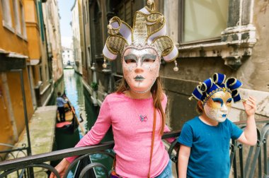 Two kids playing with famous venetian masks. Little girl and boy visiting Venice, Italy. Small tourists wearing souvenir carnival masks