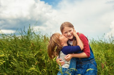 Two adorable kids, little girl and boy, playing in green wheat field. Sweet children having fun in summertime. Small brother kissing his sister