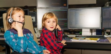 Adorable toddler boy and his sister spend the day at their parent's work in a trading room at the bank