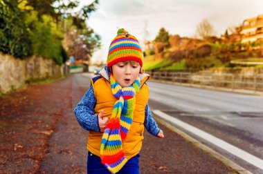 Outdoor portrait of adorable toddler boy wearing colorful hat and scarf, playing outdoors on a nice warm fall day