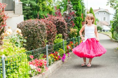 Beautiful little girl wearing bright pink tutu skirt and white top, standing next to bushes of hydrangea