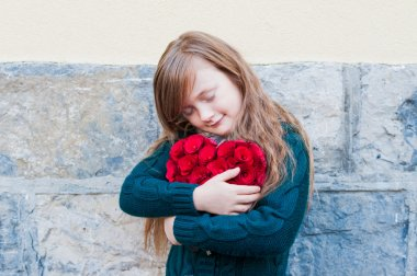 Cute little girl hagging big red heart with eyes closed