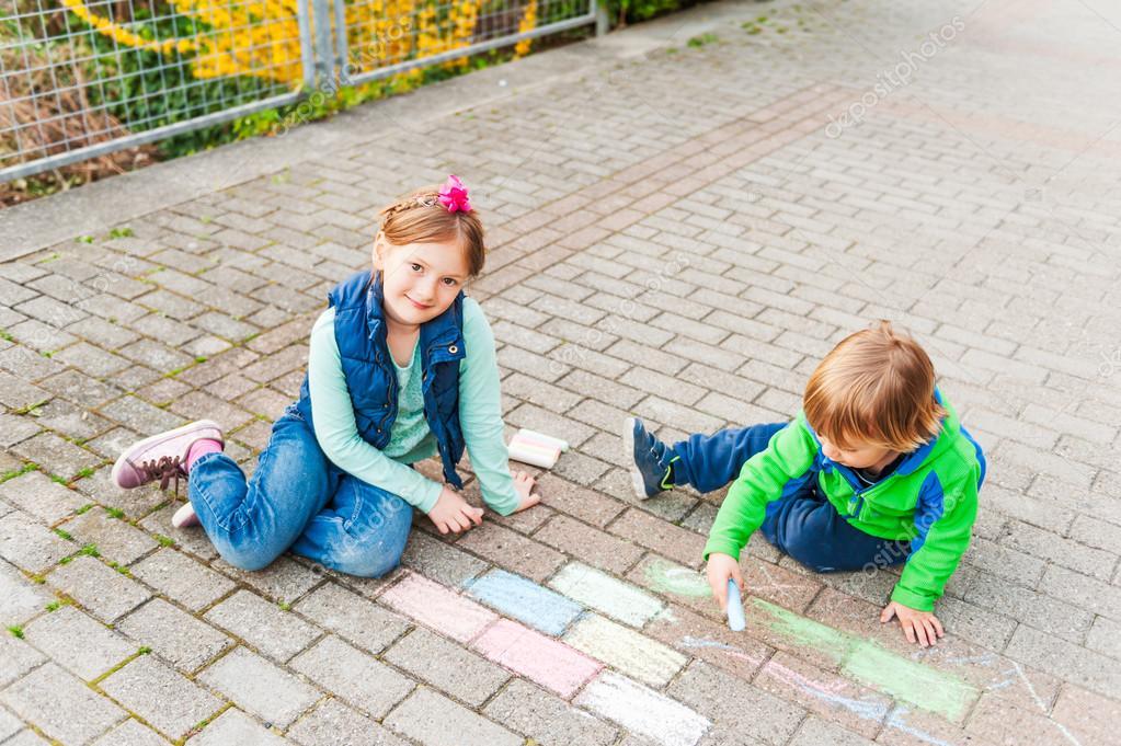 kinder spielen im freien an einem sch nen sonnigen tag mit kreide zeichnen stockfoto. Black Bedroom Furniture Sets. Home Design Ideas