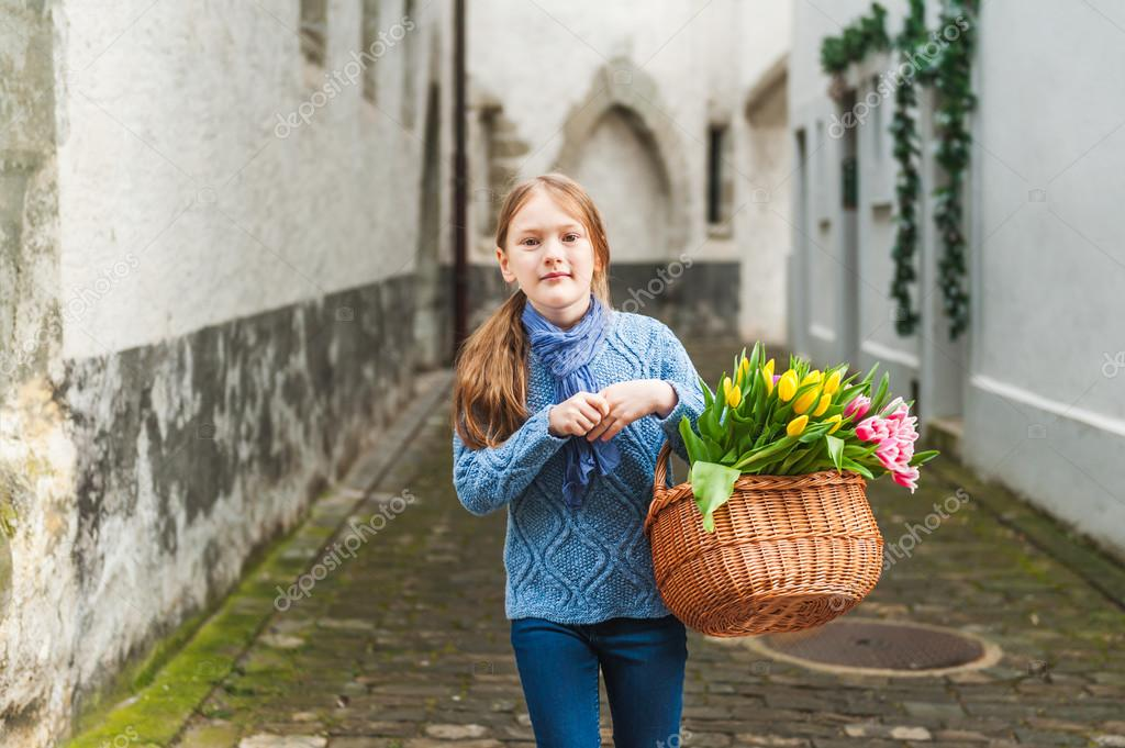 Outdoor portrait of adorable little girl of 7 years old walking in old town, holding basket full of colorful tulips, wearing warm blue pullover and scarf