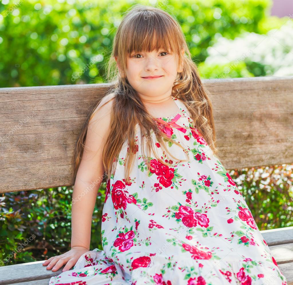 summer portrait of a cute little girl resting on a bench on a very