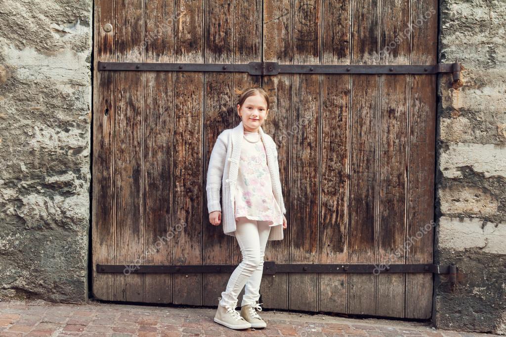 c9395c9cd Outdoor portrait of a cute little girl wearing warm white cardigan ...