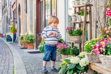 Outdoor portrait of a cute little boy, playing with flowers in front of a flower shop