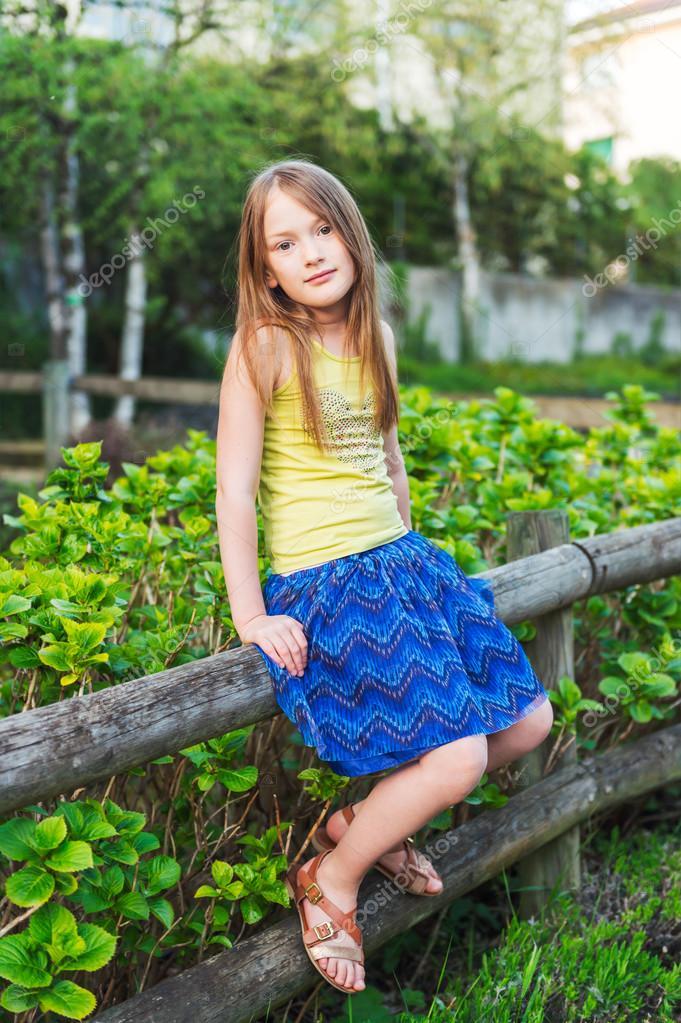 summer portrait of a pretty little girl sitting on a