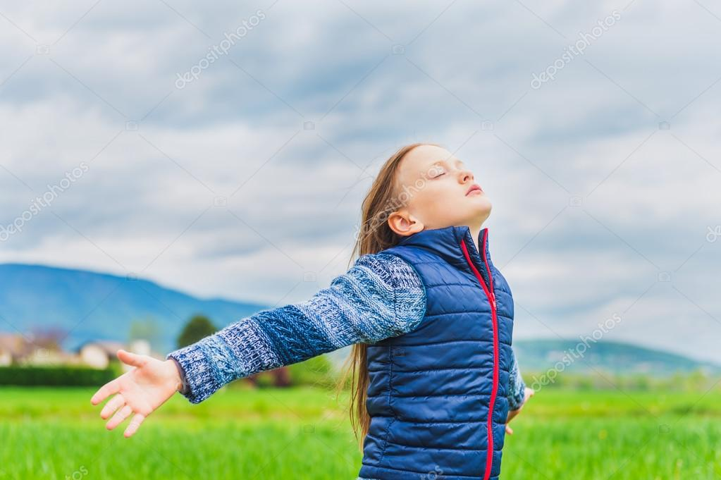 Adorable little girl playing in field with the wind, arms open wide