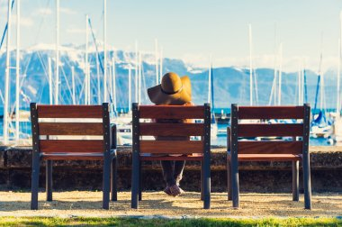 Little girl sitting on the bench and looking at amazing view, wearing big hat, back view