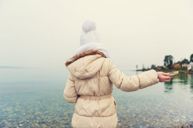 Little girl playing by the lake, throwing stones into the water on a nice cold day, wearing warm white hat, scarf and beige coat, back view, toned image
