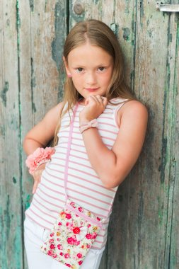 Vertical portrait of a cute little girl of 7 years old wearing many accessories