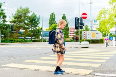 Cute little girl of 7 years girl walking to school, crossing the road in a city