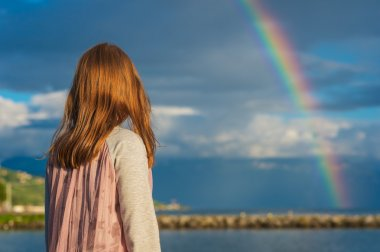Outdoor portrait of a cute little girl watching the rainbow