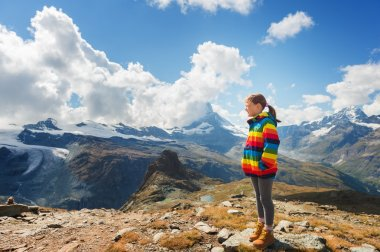 Cute little girl wearing bright rainbow colored coat and beige boots, resting in mountains,  Switzerland