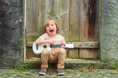 Little happy boy plays his guitar or ukulele