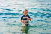 Fotografia Bambino adorabile che ha divertimento sulla vacanza di estate, giocando in mare, immagine scattata in Tropea, Calabria, Italia