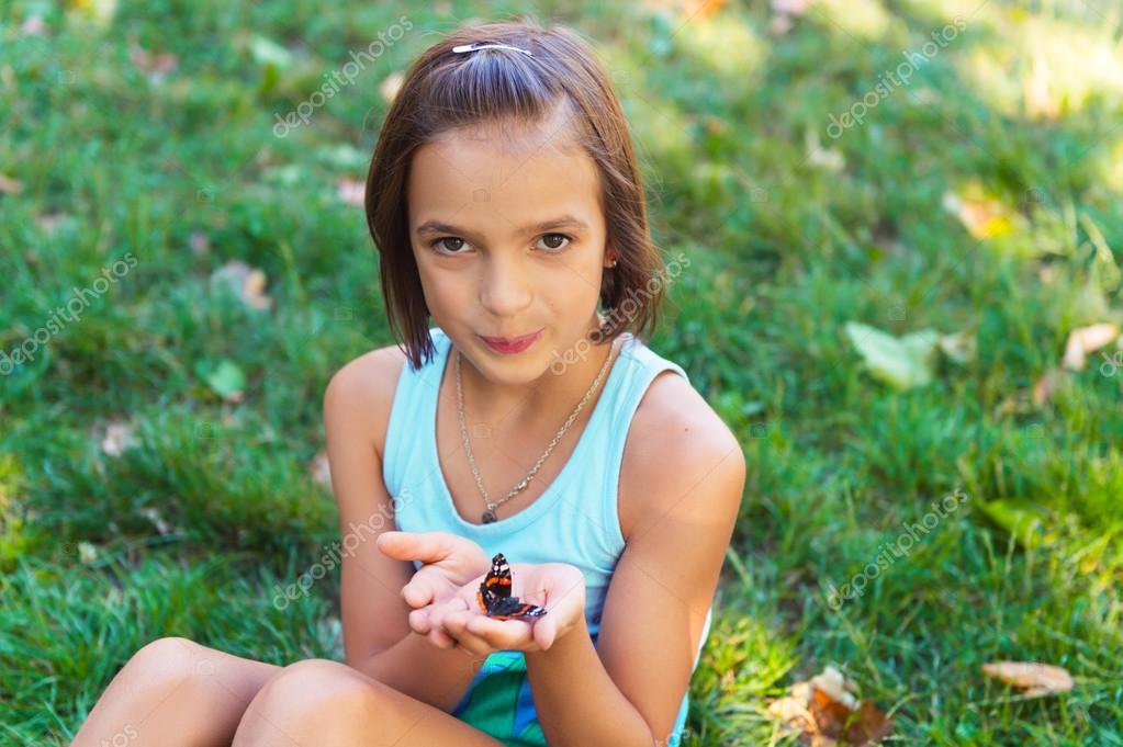 Cute Girl Playing With Butterfly Outdoors In The Park On A Nice