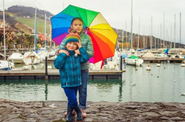 Outdoor portrait of two cute kids resting by the lake on a rainy day, hiding under big colorful umbrella