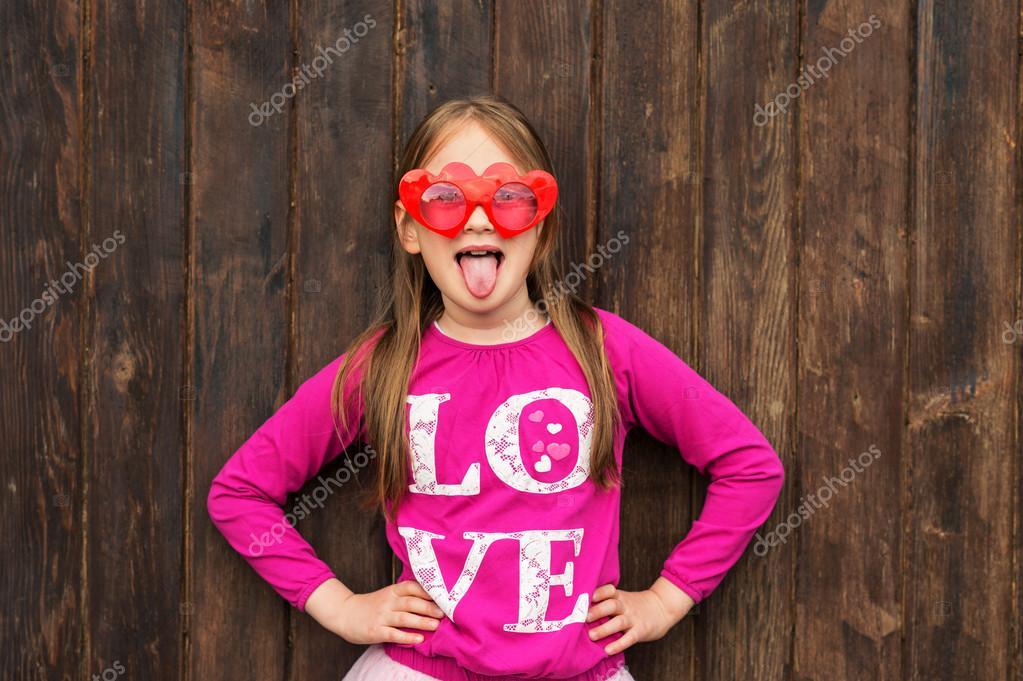 cd2ae0d5b908eb Funny portrait d une petite fille mignonne portant grosses lunettes de  soleil en forme de coeur, de la langue tirant — Image de annanahabed
