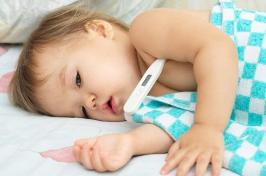 Baby ailing and lying with thermometer