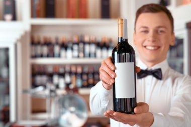 Positive sommelier holding wine bottle