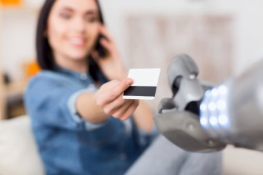 Girl giving credit card to the robot